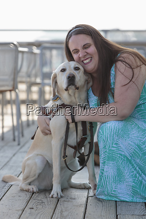 blind woman hugging her service dog