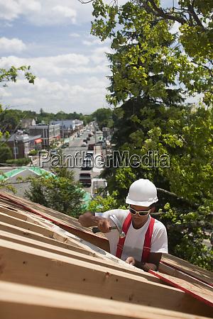 hispanic carpenter hammering on roof window