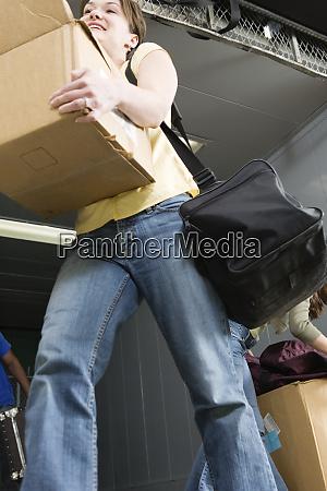 woman carrying cardboard box