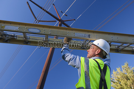 engineer placing ladder to install equipment