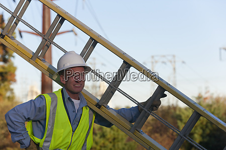 engineer holding ladder to install equipment