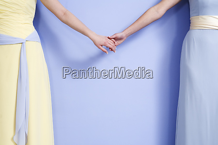 midsection of two bridesmaids holding hands
