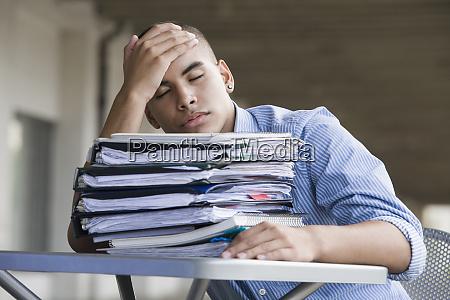 teenage boy napping at a table