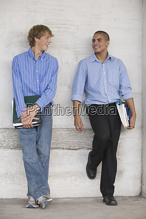 two teenage boys holding books and