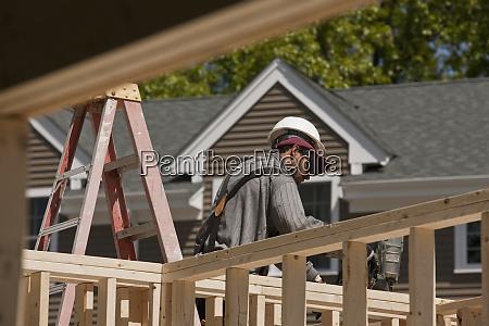 carpenter using nail gun on framing