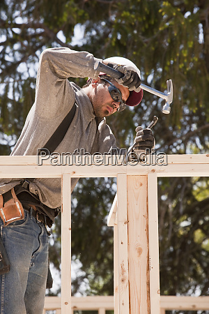carpenter hammering a pry bar to