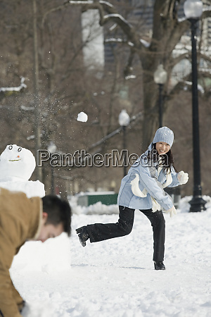 young couple playing snowball fight
