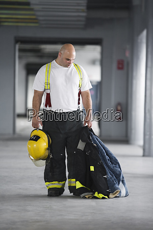 a fireman holding a jacket and