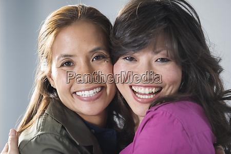 portrait of mid adult women hugging