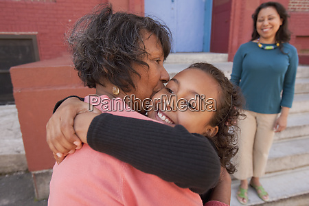 hispanic mother and grandmother seeing daughter