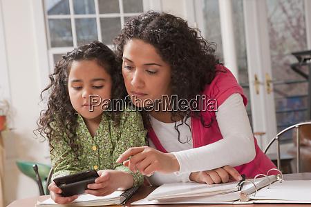 hispanic woman helping her daughter to