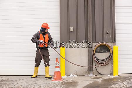 transportation engineer unrolling hose at an