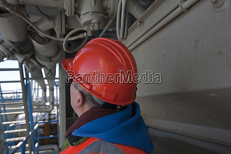 engineer examining insulated liquid delivery pipe