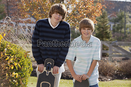 two brothers standing with skateboards