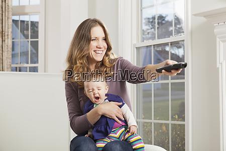 woman watching tv with sleepy baby
