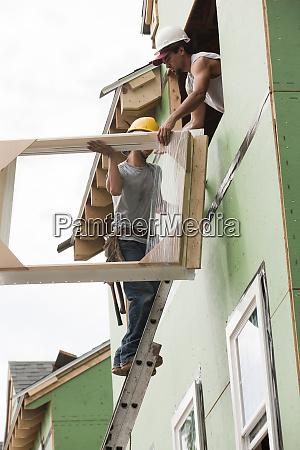 carpenter on ladder handing window frame