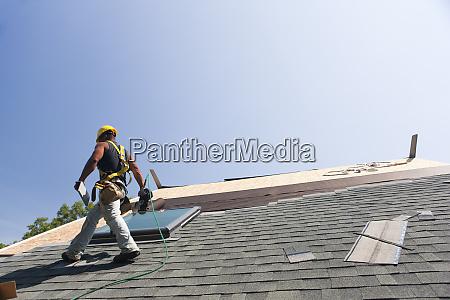 roofer installing flashing on skylight