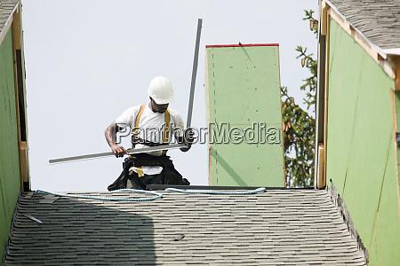 roofer preparing flashing on peak of