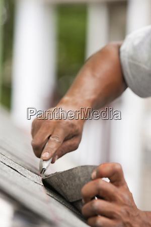 carpenter trimming shingle at string line