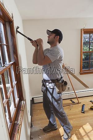 hispanic carpenter removing window framing from