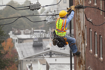 cable lineman holding onto pole while
