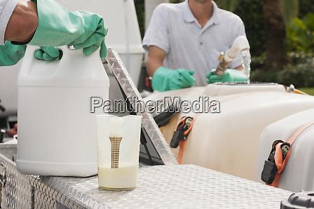 pest control technicians mixing chemicals at