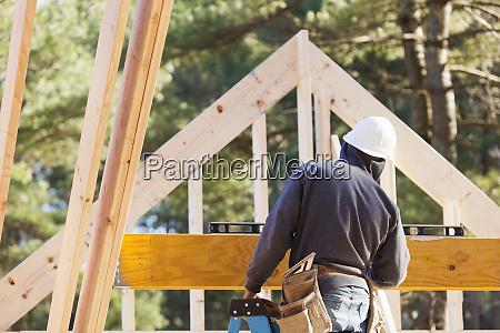 carpenter using horizontal level on beam