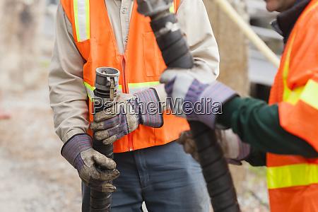 environmental engineers examining hose coupling for