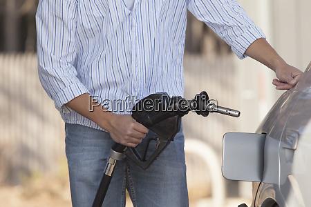 man refueling his car at the