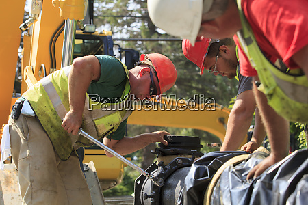 construction workers using torque wrench to