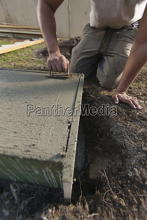 hispanic carpenter using finish trowel to