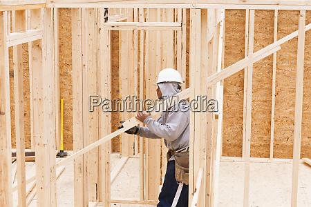carpenter carrying studs in framed house