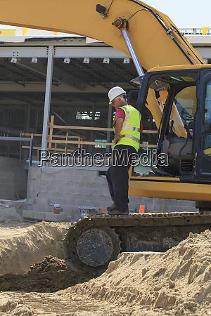 construction engineer standing on the excavator