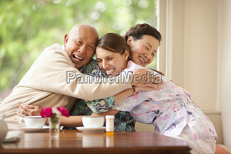 senior couple hugging their nurse