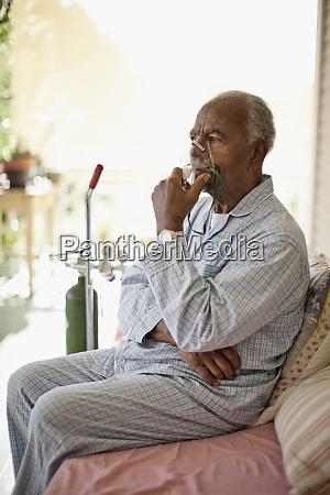 unwell elderly man uses oxygen mask