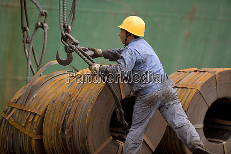male construction worker attaching cables to