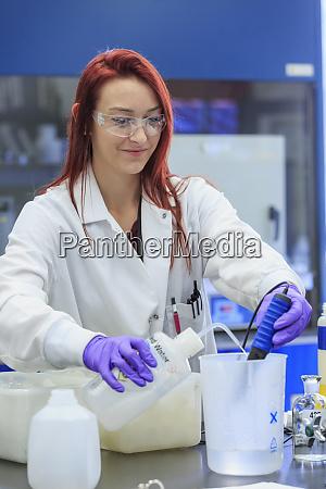 lab chemist adding distilled water while