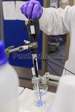 lab technician adding reagent to sample