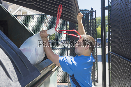 man with down syndrome throwing garbage