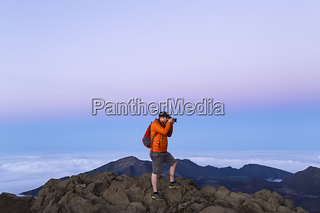 tourist photographing on a mountain summit