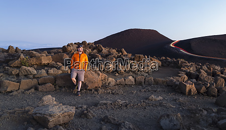 man standing against rugged rocks above