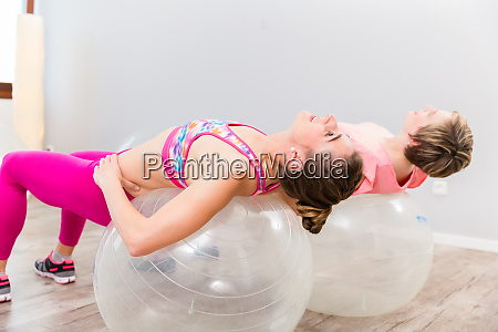 young women practicing pilates ball exercise