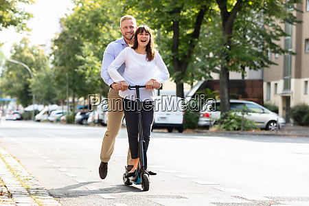 smiling young couple riding on electric