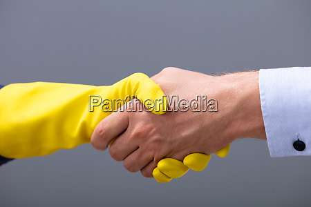 businessman and janitor shaking hands together
