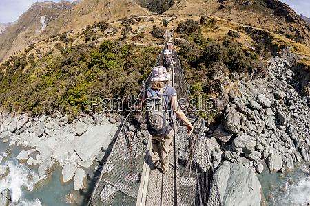 hikers cross a footbridge over the
