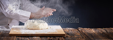 chef or baker dusting dough with
