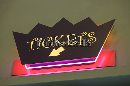 a sign pointing to ticket sales