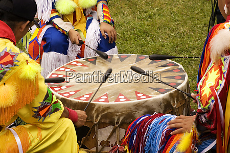 indians around a drum at a