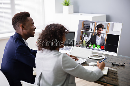 businesspeople videoconferencing with colleague