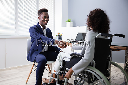 businessman shaking hands with disabled businesswoman